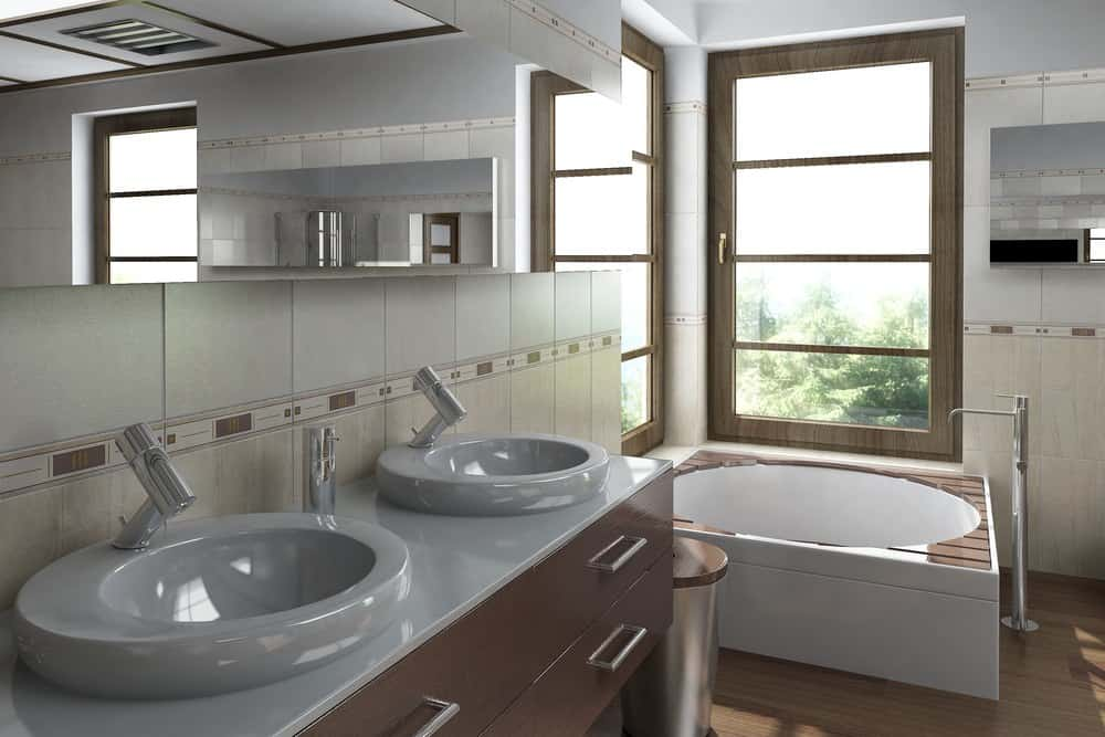 An Asian-style primary bathroom boasting a stunning couple of vessel sink along with a round deep soaking tub near the windows.