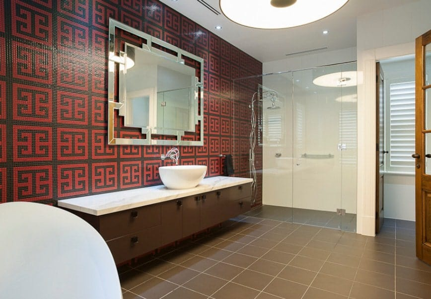 This primary bathroom boasts a decorated wall in Asian style and has a long sink counter with a single vessel sink. The room also offers a walk-in shower room and a freestanding deep soaking tub.
