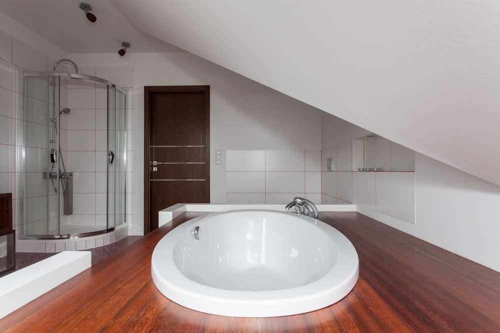 White primary bathroom with an Asian-style deep soaking tub. There's a corner walk-in shower as well.