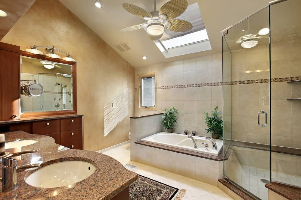 A primary bathroom with a tall ceiling featuring a skylight. The room offers a double sink and a drop-in tub along with a walk-in corner shower room.