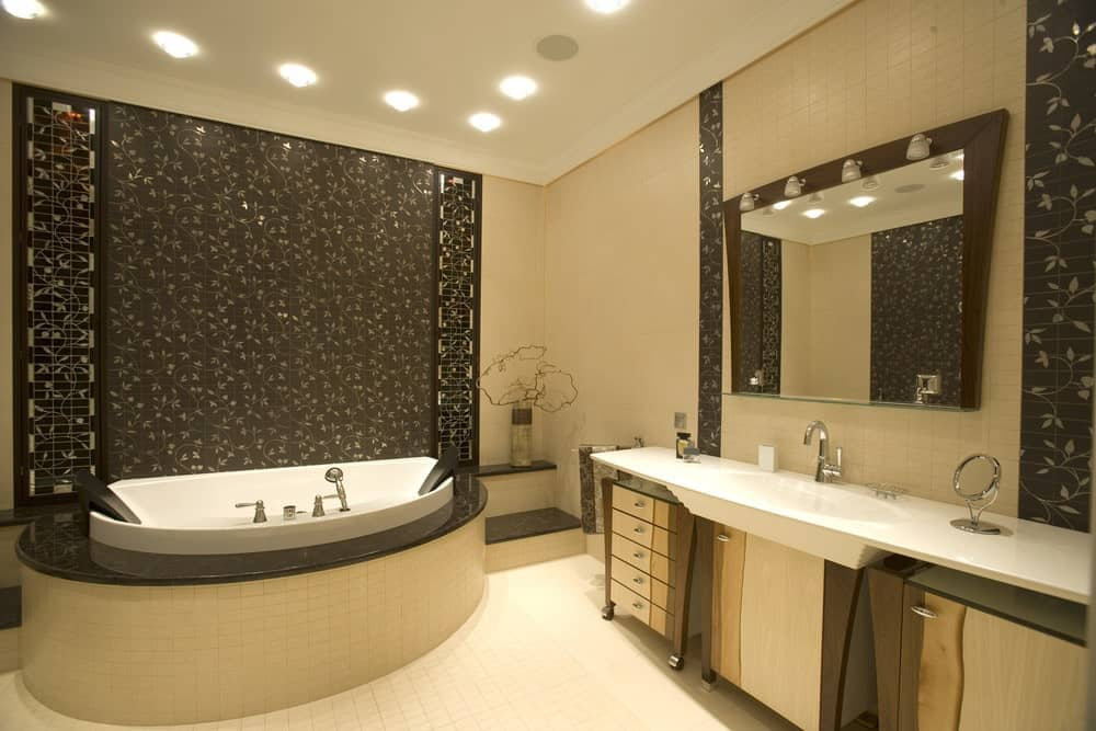 A beautiful Asian-style primary bathroom with a decorated wall near the deep soaking tub with a nice-looking platform. The area is lighted by lined-up recessed lights.