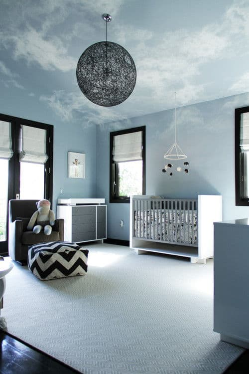 Marvelous nursey features a textured area rug and a black spherical chandelier that hung from the vaulted ceiling painted with serene sky mural. It includes a white crib and gray armchair paired with chevron ottoman.