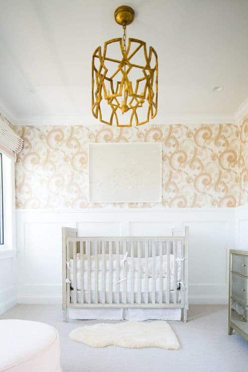 A stylish gold chandelier adds a stunning accent in this nursery clad in peach swirl wallpaper and white wainscoting. It has a natural wood crib and a white faux fur rug that lays on the gray carpet flooring.