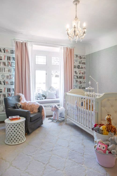 The classy nursery offers a white tufted crib and gray skirted armchair paired with a perforated side table. It includes a fancy chandelier and a window seat nook covered in pink and white sheer curtains.