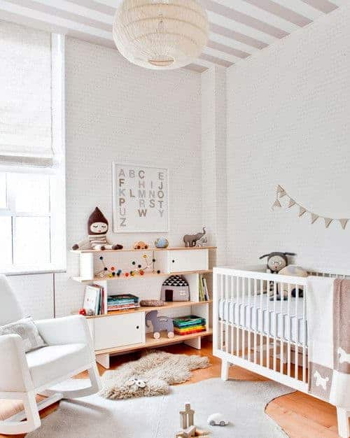 White nursery decorated with alphabet wall art and a spherical woven chandelier that hung from the striped ceiling. It has a white crib and a cushioned rocking chair over layered rugs and hardwood flooring.