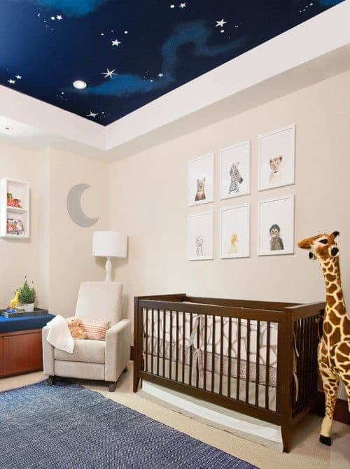 A stunning custom ceiling with night sky mural adds whimsical vibes in this baby nursery designed with moon and animal portraits mounted above the wooden crib.