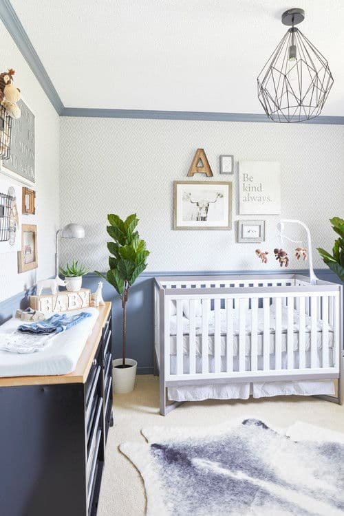 Fresh nursery boasts gallery walls and a cowhide rug that lays on the carpet flooring. It includes geometric chandelier and a white crib flanked by green potted plants.