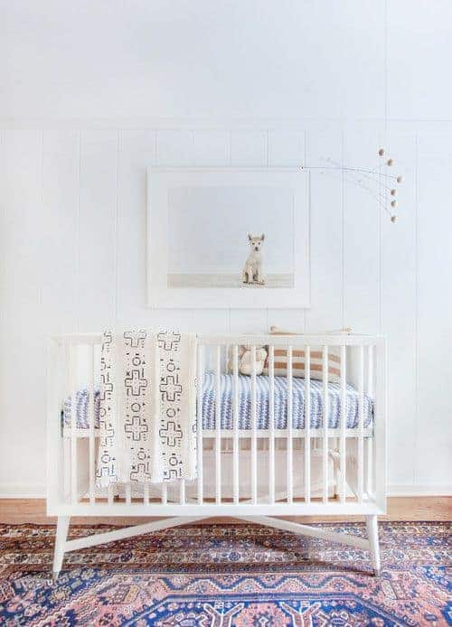 A lovely dog wall art hangs above the sleek crib in this white nursery with beadboard wall and hardwood flooring topped by a classic area rug.