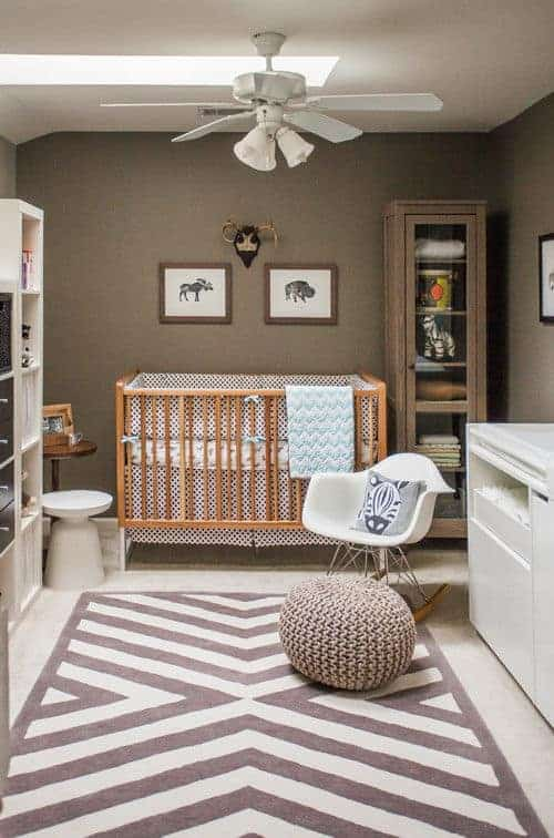 Modern nursery accented with a striking patterned rug over carpet flooring. It has a modern white chair and a wooden crib with interesting wall arts on top.