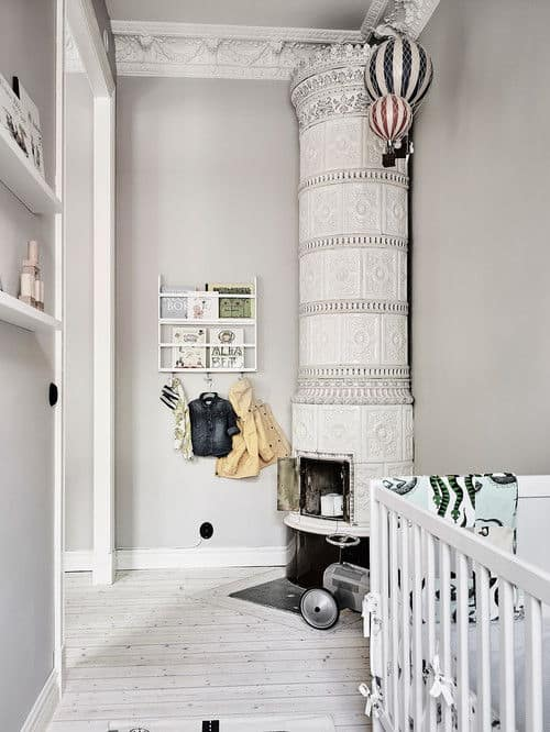 A gorgeous corner fireplace designed with intricate details is the highlight in this baby nursery with floating shelves and a white crib over light wood plank flooring.
