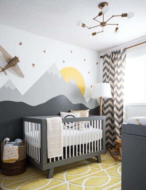 This nursery showcases chevron drapes and a gray crib with a mountain mural backdrop. It is illuminated by a brass chandelier and a traditional floor lamp.