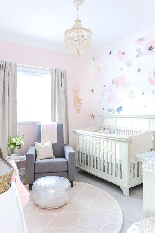 Charming nursery with a white crib and gray armchair paired with a silver ottoman over a round patterned rug. It is lighted by a boho chandelier and natural light from the picture window covered in blackout draperies.
