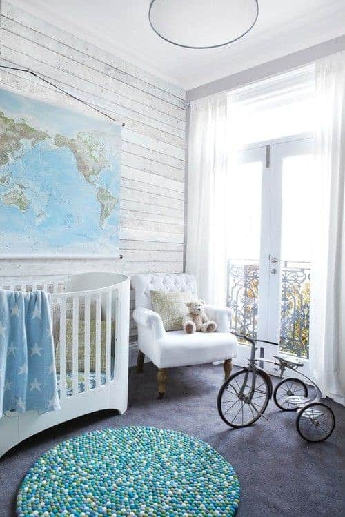 Natural light streams in through the French door that opens to the balcony framed with ornate wrought iron railings. This nursery has a gorgeous round rug and a tufted armchair next to the white crib under a map tapestry.