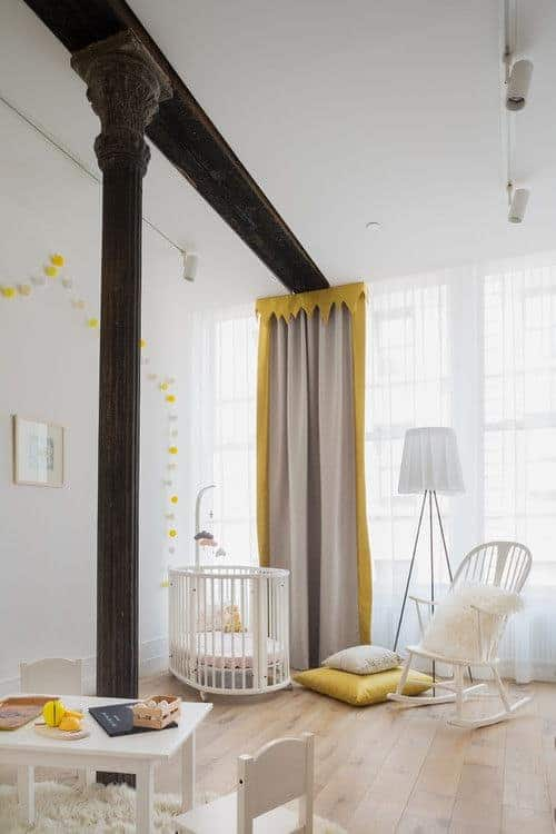 Yellow valance, pillow and pompom garland adds a pop of color in this neutral nursery lined with a vintage column. It has a white table and crib that matches the rocking chair lighted by a tripod floor lamp.