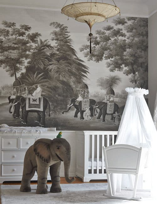 Elephant themed nursery with a unique chandelier and white cabinet complementing with the crib and rocking bassinet that's covered in a round canopy.