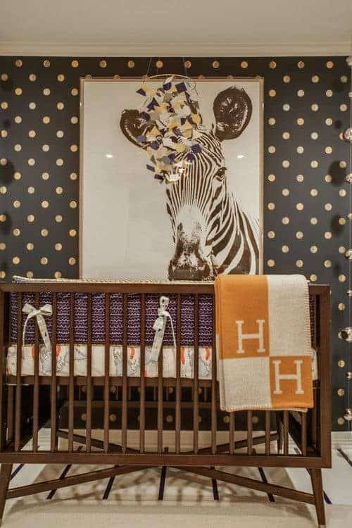 A black dotted wall mounted with a zebra portrait sets a gorgeous backdrop to the wooden crib that sits on a carpet flooring topped by a striped runner.