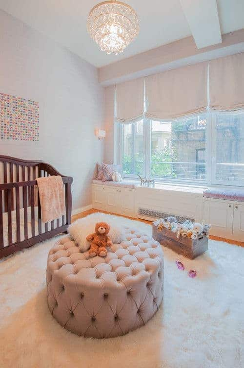 A fancy chandelier illuminates this nursery offering a wooden crib and round tufted ottoman over a white furry rug. It includes a lovely artwork and a seat nook by the glass paneled windows dressed in blush roman shades.