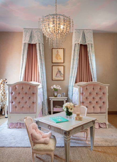 Shared nursery perfect for twin princesses. It showcases pink tufted cribs with canopies along with a classy table and chairs lighted by a gorgeous chandelier.