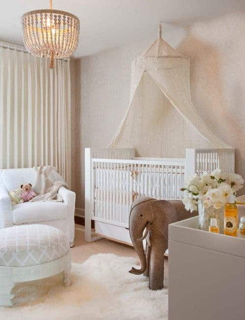 A boho chandelier hangs over the round ottoman sitting on a white faux fur rug over carpet flooring. There are white armchair and skirted crib with a canopy net overhead.