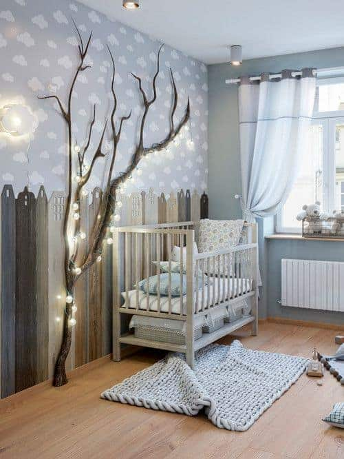 This nursery is designed with city wallpaper and a tree wrapped in fairy lights. It has a knitted rug and a sleek crib with storage baskets underneath.