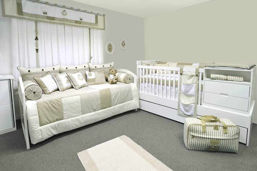 Gender-neutral baby nursery with a crib, changing table, and a seating area.
