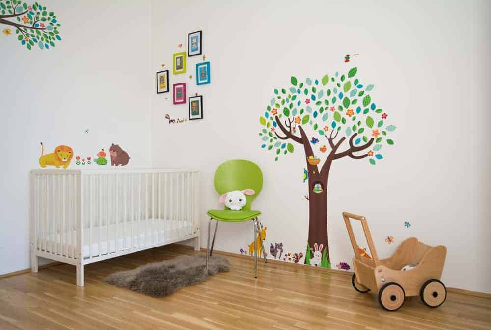 This nursery showcases hardwood flooring and white walls designed with multicolor framed artworks along with a tree and animal stickers. It has a white crib, green round back chair and a brown shaggy rug.