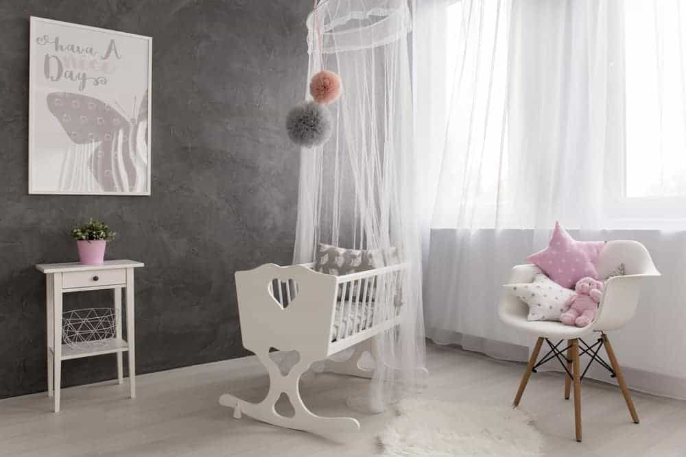 Airy nursery offers a modern white chair and rocking cradle with canopy net and hanging pompoms on top. It includes a console table with a geometric bowl underneath and a lovely artwork mounted on the concrete wall.