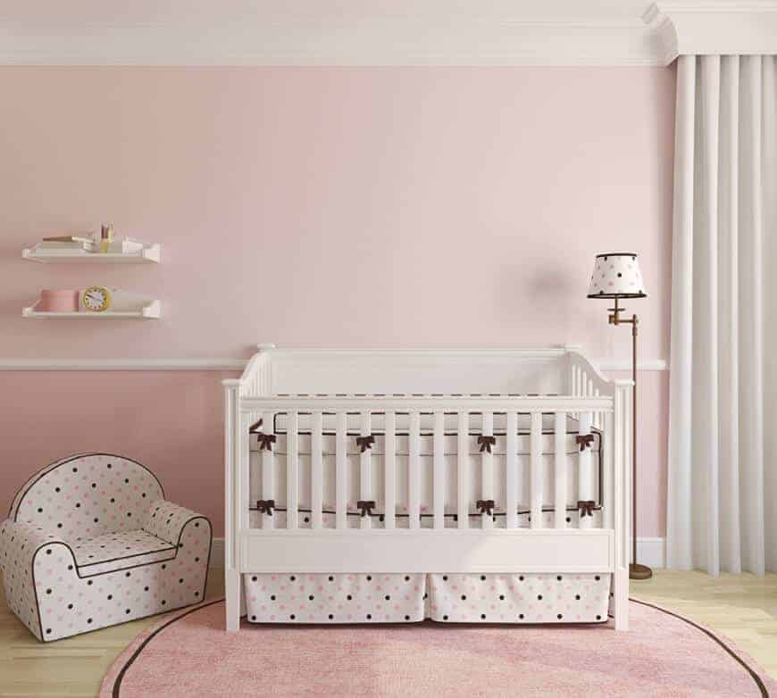A cute dotted armchair matches the skirted crib and floor lamp in this pink nursery with floating shelves and a round area rug that lays on the light hardwood flooring.