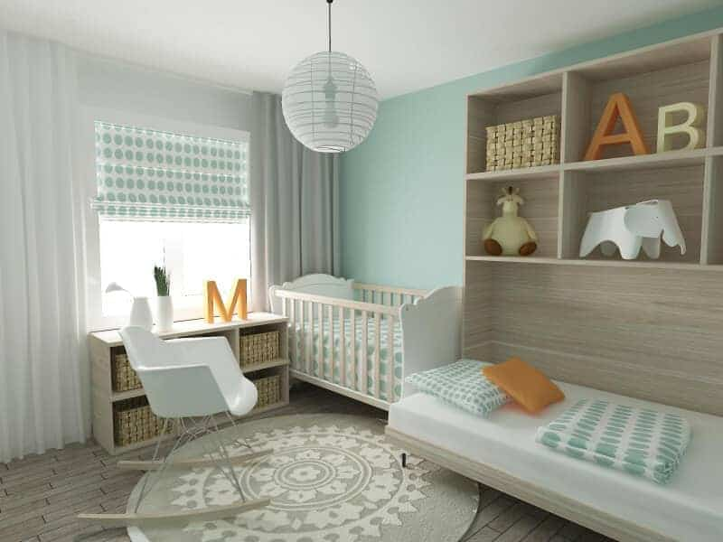Fresh nursery with a white crib and rocking chair that sits on a gray round rug lighted by a spherical pendant light. It has built-in shelving and bed fixed on the mint green wall.