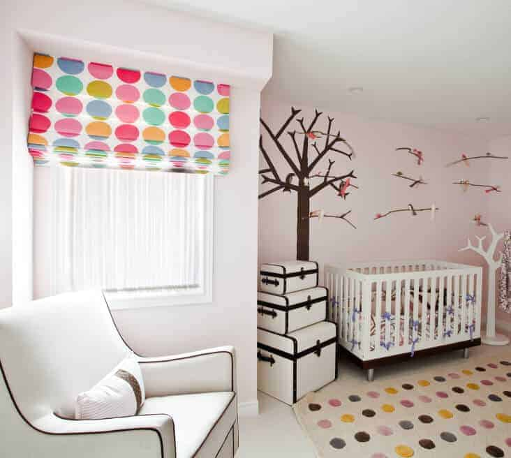 A multicolor dotted roman shade and rug add a nice accent in this nursery with a white armchair and crib situated in between storage boxes and coat rack.