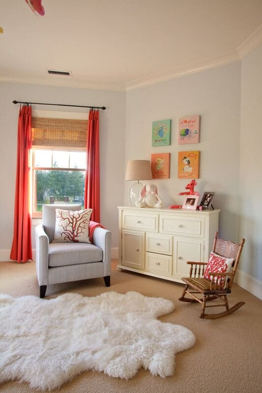 A white faux fur rug lays on the beige carpet flooring in this nursery offering a gray armchair and wooden rocking chair with a cream cabinet in the middle accented by animal wall arts.