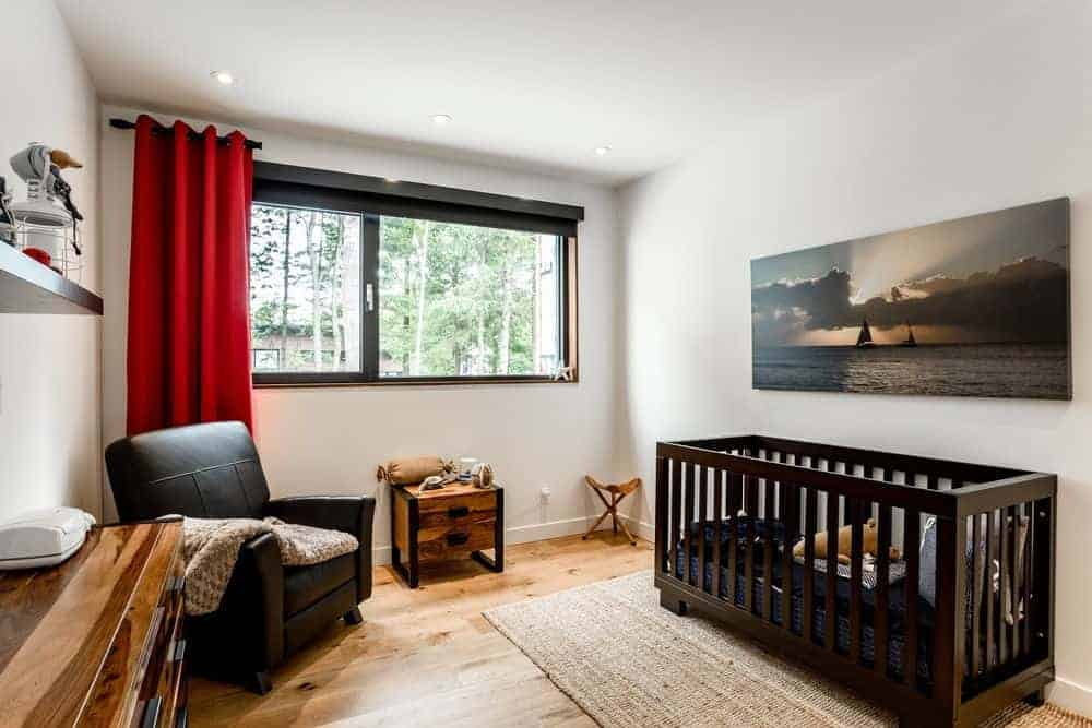 Cozy nursery with a black leather armchair and an ocean canvas mounted above the crib that sits on a jute rug. It has natural hardwood flooring and aluminum framed windows covered in red drapery.
