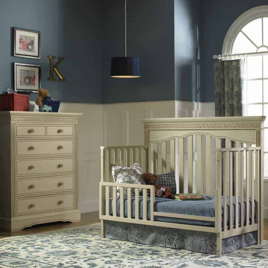 A drum pendant light illuminates this classic nursery showcasing a skirted crib and drawer chest accented with black framed wall arts. It has a floral area rug and patterned drapes covering the arched window.