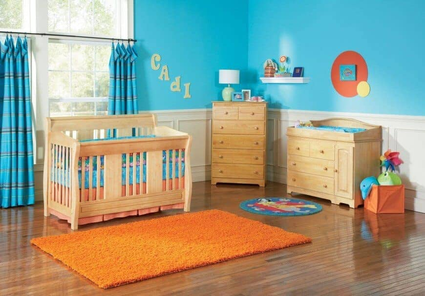 Blue nursery clad in white wainscoting features light wood furnishings and an orange rug that lays on the wide plank flooring.
