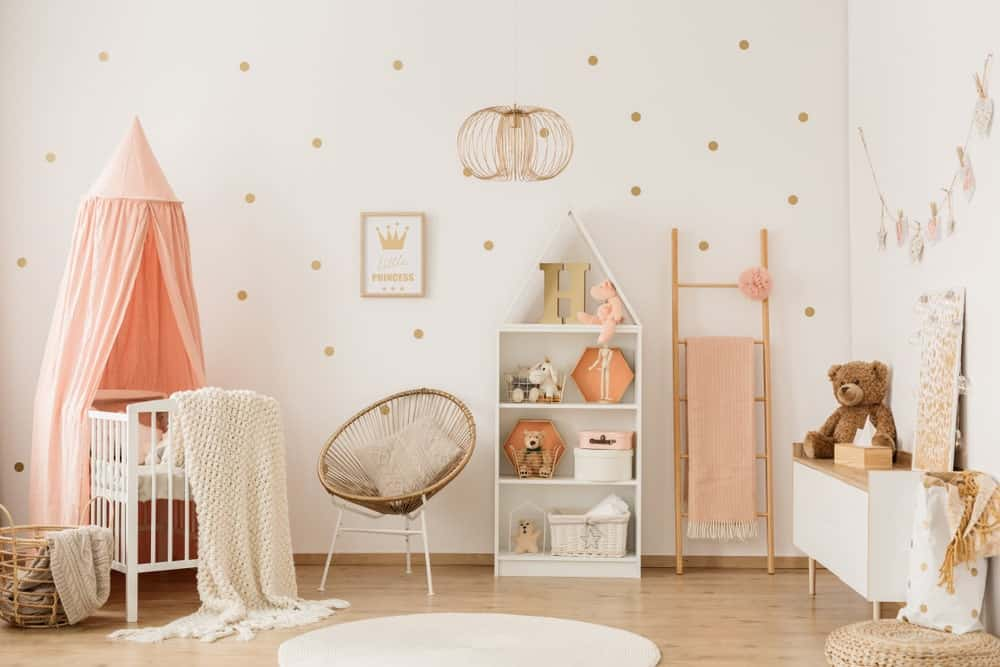 A lovely copper wire pendant light illuminates this charming nursery featuring a round chair and white crib with a peach canopy overhead. It is accompanied by a shelving unit, a wooden ladder that serves as rack and a console table topped with a teddy bear and cute artwork.