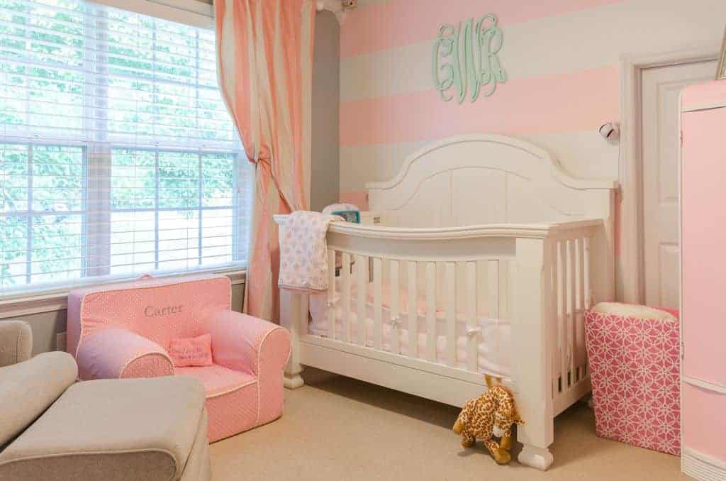 Airy nursery features a pink dotted mini armchair and a white crib placed against the striped accent wall. It has carpet flooring and glazed windows bringing natural light in.