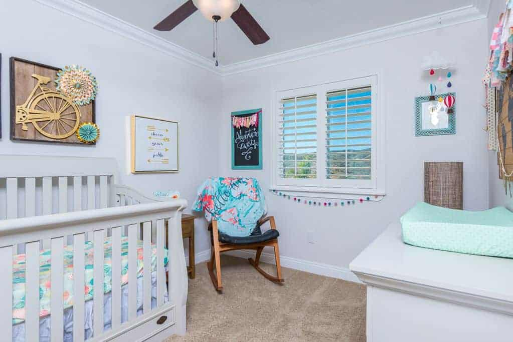 Classic nursery surrounded by various wall arts and a glazed window covered with white shutter. It has a white crib and a rocking chair paired with wooden side table.