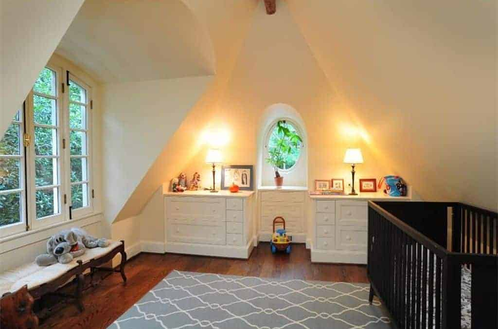 Warm nursery with vaulted walls and hardwood flooring topped by a gray patterned rug. It includes a dark wood crib and white cabinets lighted by traditional table lamps.