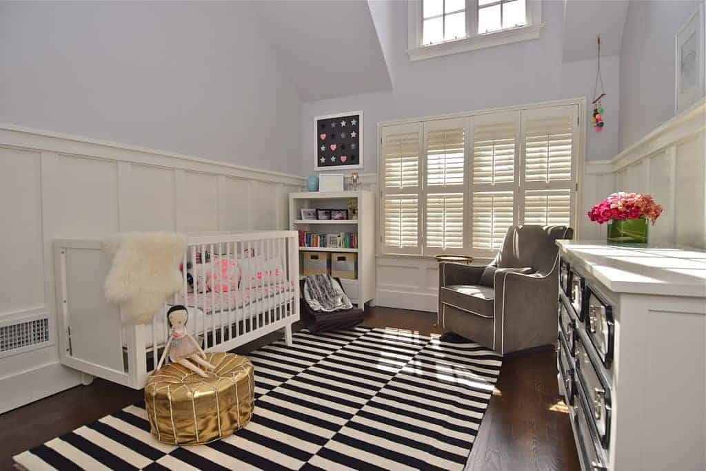 A cute doll sits on the gold ottoman over a black and white striped rug in this nursery boasting a gray armchair and white crib placed against the wainscoted lower wall.
