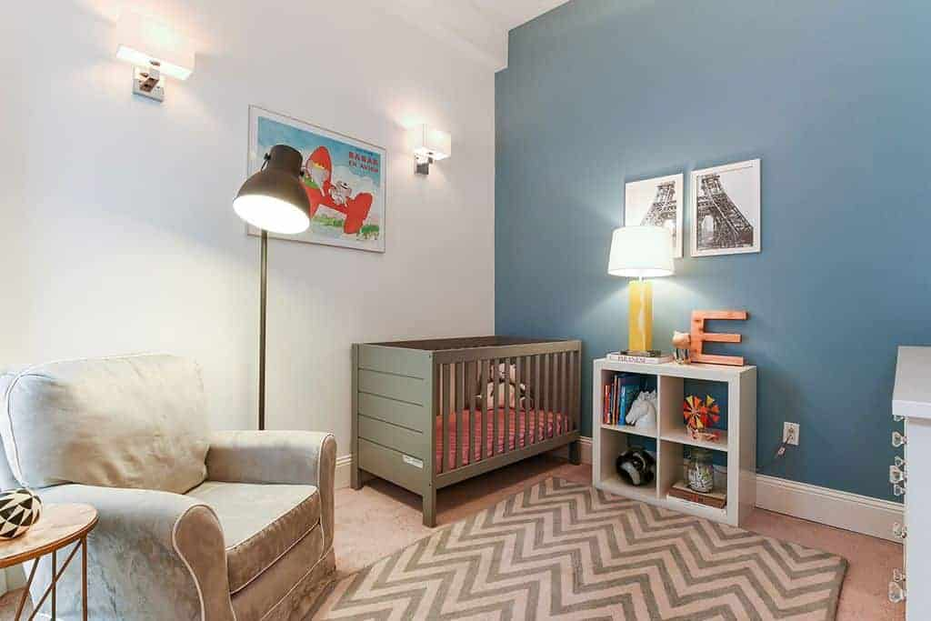 This nursery is furnished with a wooden crib and taupe armchair lighted by a black dome floor lamp. It includes a chevron rug and open shelving topped with a yellow table lamp.