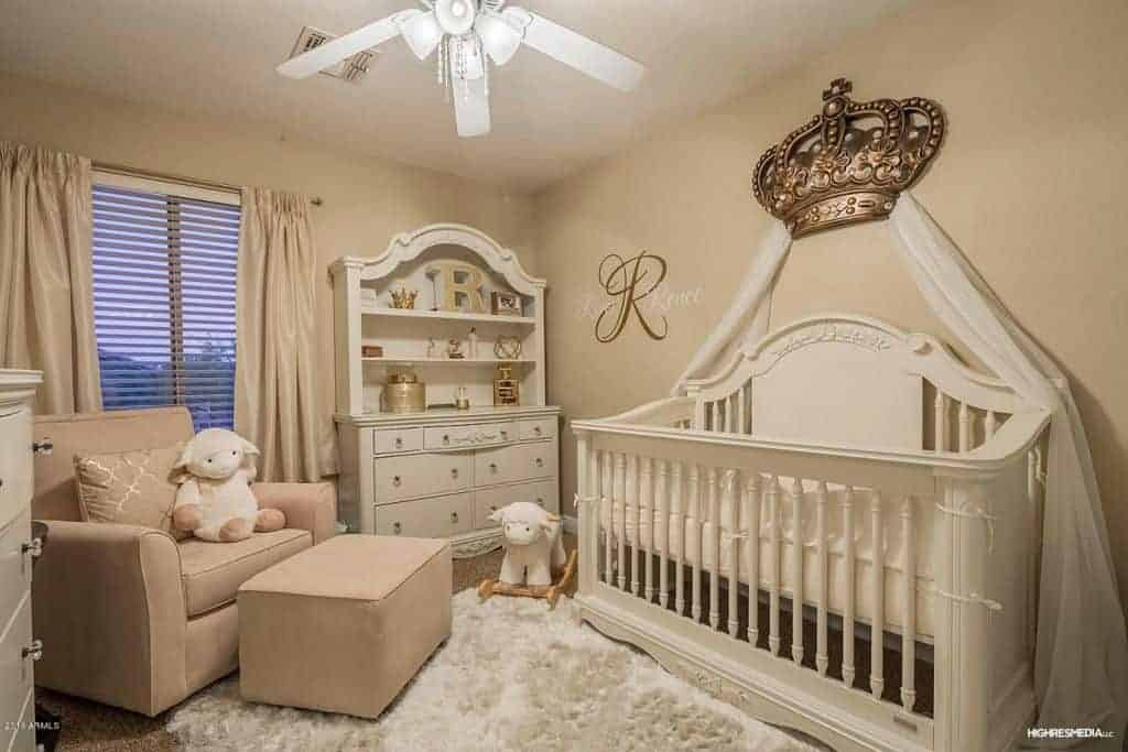 Charming nursery offers a blush armchair and ottoman along with white cabinet and crib accented with a gorgeous crown canopy on top. It has a shaggy area rug and a louvered window covered in silk drapes.