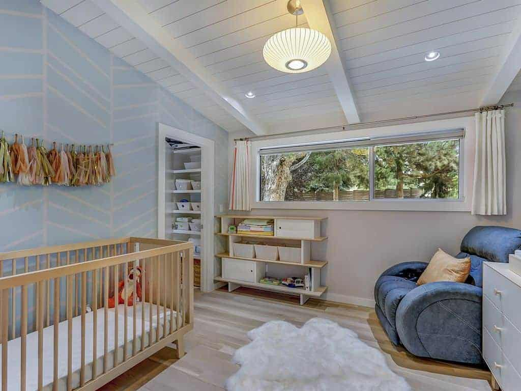 Cozy nursery features a wooden crib, blue recliner and a white faux fur rug that lays on the hardwood flooring. It is illuminated by a round pendant and recessed lights fitted on the shiplap ceiling with exposed beams.