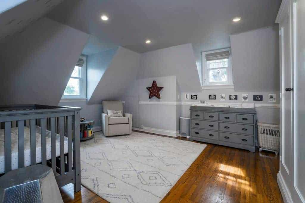 Gray nursery with vaulted walls and carpet flooring topped by a patterned area rug. It includes an upholstered armchair and crib that matches the dresser flanked by trash and laundry bins.