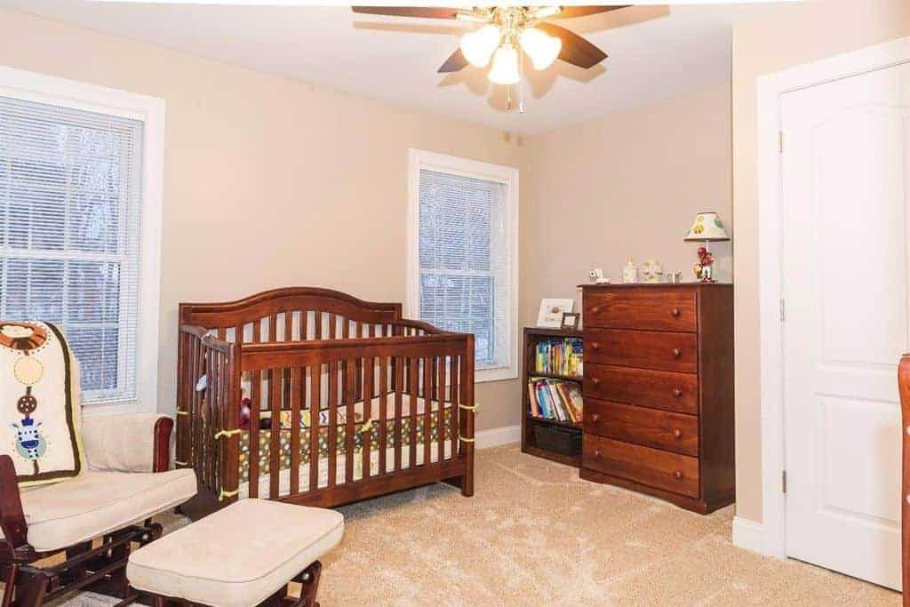 A wooden crib complements the drawer chest and cushioned chair paired with a matching ottoman in this nursery with carpet flooring and ceiling fan with lights illuminating the entire space.