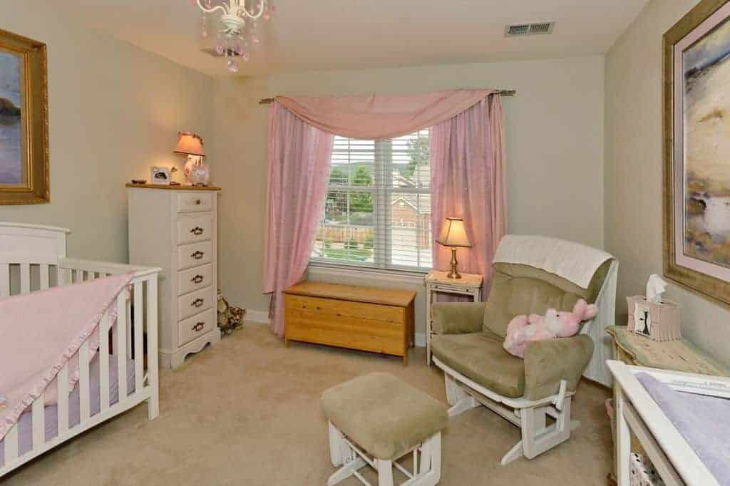 Beige nursery with subtle pink accents from the drapes, blanket and bunny that sits on a cushioned armchair matching with the ottoman and carpet flooring.