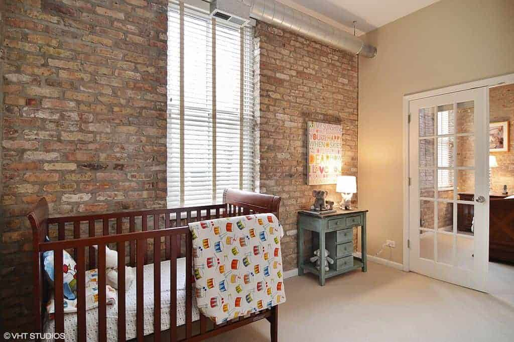 A stone brick accent wall adds texture in this industrial nursery with carpet flooring and a French door that leads out to a bedroom. It includes a wooden crib and distressed cabinet with a table lamp and artwork on top.