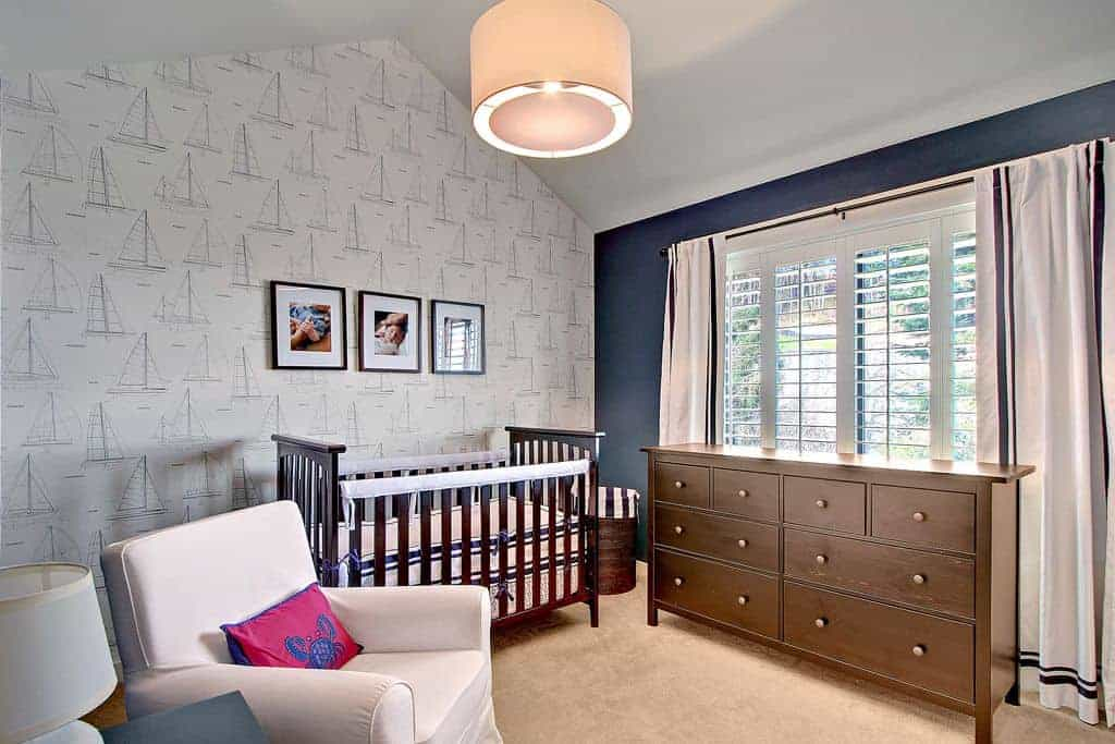 Black framed photos hang over the dark wood crib accompanied by a wooden cabinet and gray skirted armchair that's accented with a pink pillow with crab print.