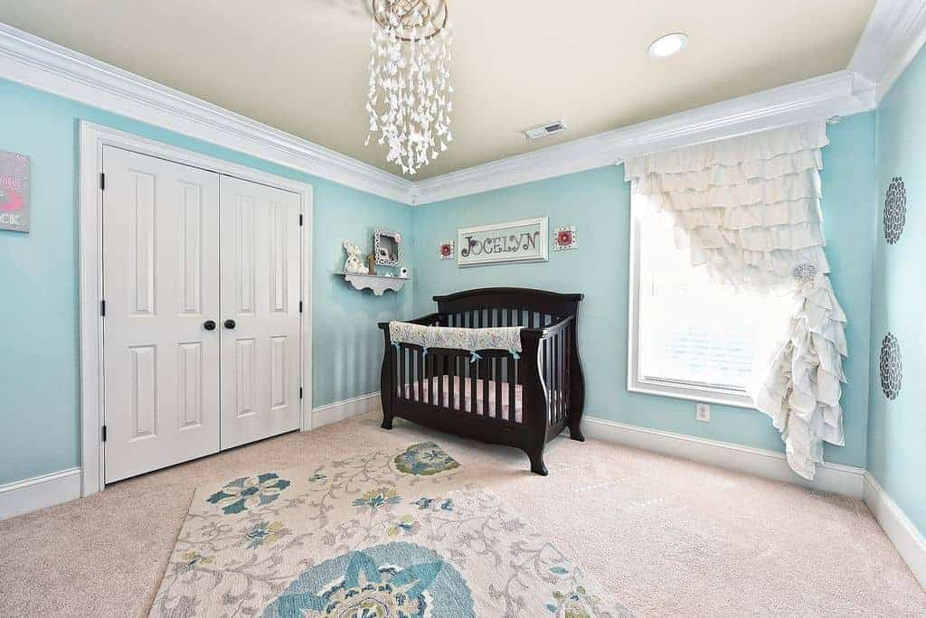 A white double door opens to this aqua nursery showcasing a charming floral rug and dark wood crib with a framed baby's name on top.