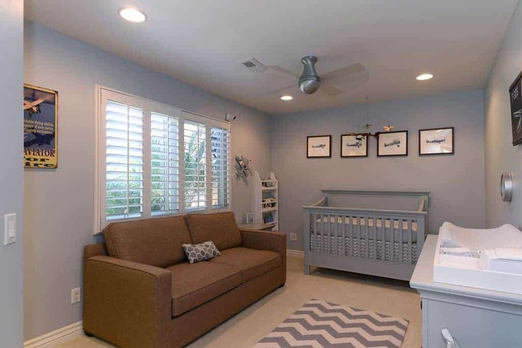 A brown sectional sofa stands out in this gray nursery showcasing a comfy crib and chevron rug that lays on the carpet flooring.