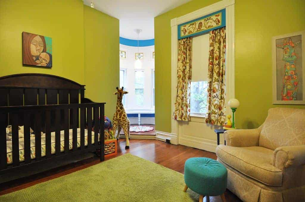 A vibrant green nursery boasts a skirted armchair paired with a round ottoman along with a dark wood crib accented with a mother and child painting.